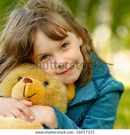 The small beautiful girl embraces an amusing bear cub against the summer nature. - stock photo