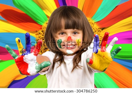 The small beautiful girl has stretched to a camera of a palm soiled in a paint of different colors, smiles - stock photo