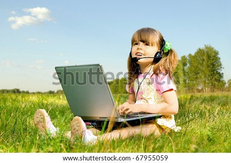 The small beauty girl works on a computer, sit on green lawn, Smile - stock photo