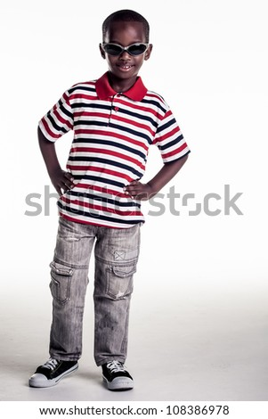 The small boy is dressed in a outfit that gives him a cool, confident look. - stock photo