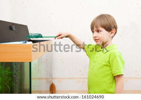 The small boy wants to fish in an aquarium - stock photo