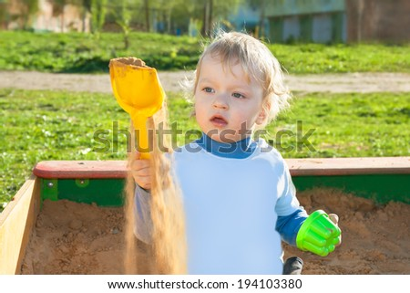 the small child plays in a sandbox at a playground - stock photo