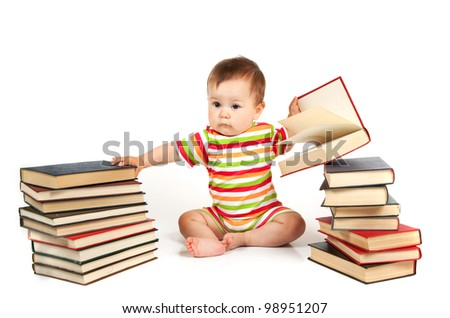 The small child sits near a pile of books