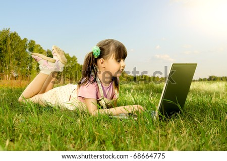 The small cute girl game on a computer, lie on a beautiful green lawn, Smile - stock photo
