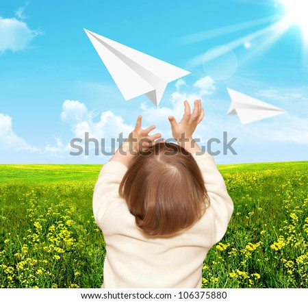 The small girl plays with the paper airplane. Nature