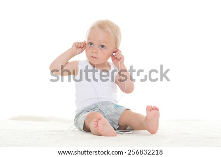 The small happy child with a mp3 player sits on a floor and listens to music