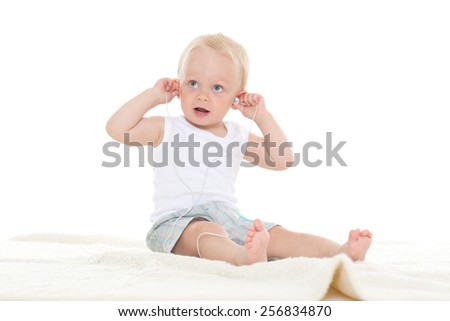 The small happy child with a mp3 player sits on a floor and listens to music - stock photo
