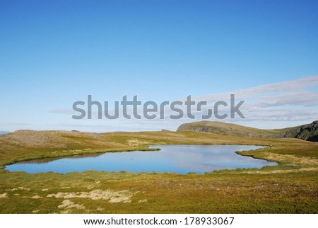 The small lake is reflecting the blue sky. Soroya is a large island in western Finnmark of Norway.