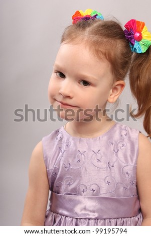 The small lovely girl in violet dress on gray background