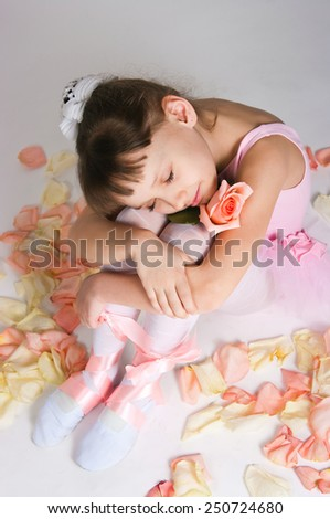 The small tired ballerina sits on a floor in rose-petals - stock photo