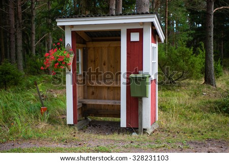 The Small wooden bus stop in the Finnish forest.