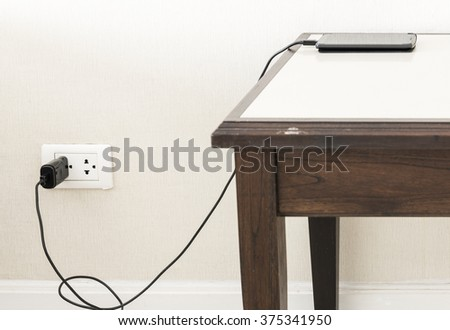The Smart phone charger with wall outlet on the wooden table,select focus - stock photo