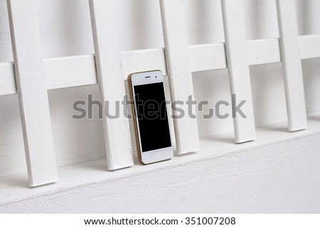 The smartphone in a white interior with a clean screen off - stock photo