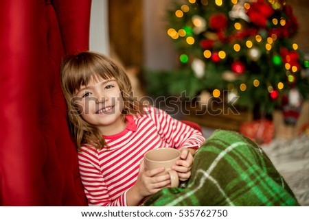 The smile little girl little girl holding a mug and looks dreamily on the tree in anticipation of holiday. The concept of Christmas