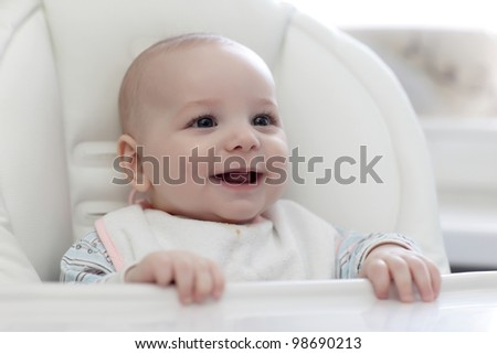 The smiling baby in highchair at home
