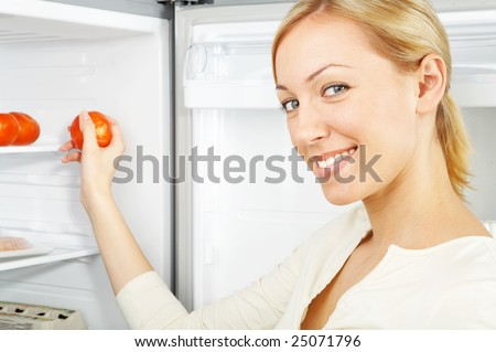 The smiling blonde takes a tomato from a refrigerator - stock photo