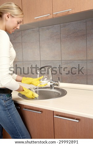 The smiling blonde washes a glass on kitchen