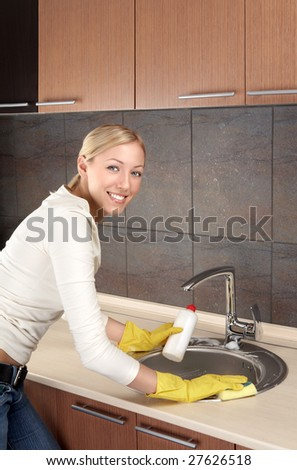 The smiling blonde washes ware in a bowl on kitchen - stock photo