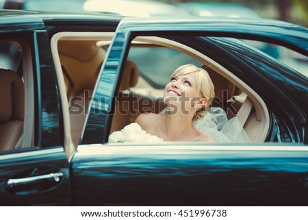 The smiling  bride sits in car