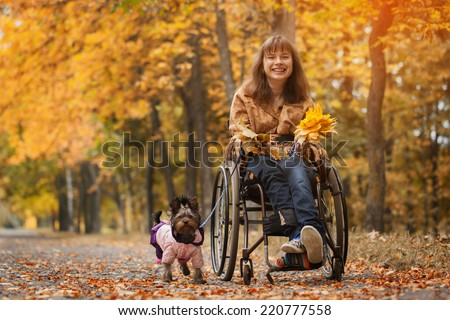 the smiling cheerful girl on a wheelchair with the dog in autumn road - stock photo