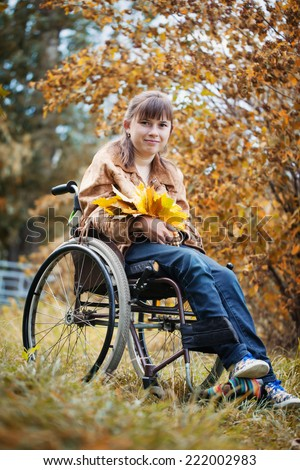 The smiling disabled girl in wheelchair in the autumn park