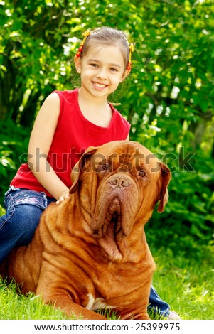 The smiling girl astride the big dog of breed FRENCH MASTIFF, DOGUE DE BORDEAUX - stock photo