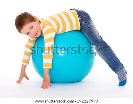 The smiling little boy lies on the big blue ball, looking at the camera, isolated on white background - stock photo