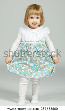The smiling little girl staying and holding her beautiful dress; neutral background - stock photo