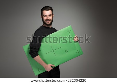 The smiling man as businessman with green panel on gray background. Positive human emotions and advertising of something - stock photo