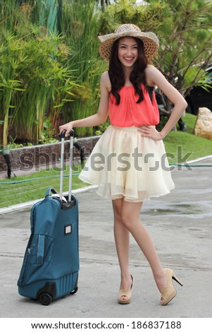 The smiling woman and briefcase prepared the travel - stock photo