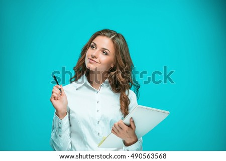 The smiling young business woman with pen and tablet for notes on blue background