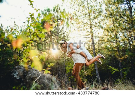 the smilling girl jumps on the guy's back - stock photo