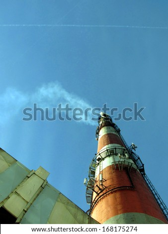 The smoke from the chimney and flue gases from planes - the impact of emissions from smokestacks and exhaust of aircraft on the greenhouse effect - stock photo