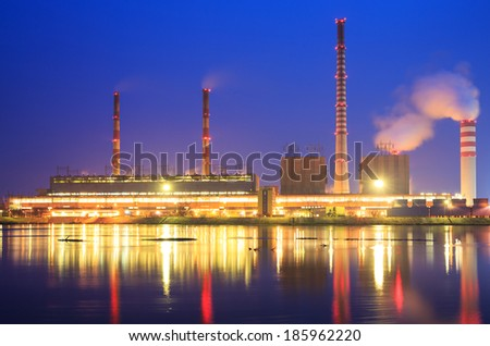 The smoke from the chimney power plant at night  - stock photo