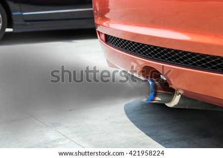 The smoke from the exhaust of a car when the engine starts. - stock photo