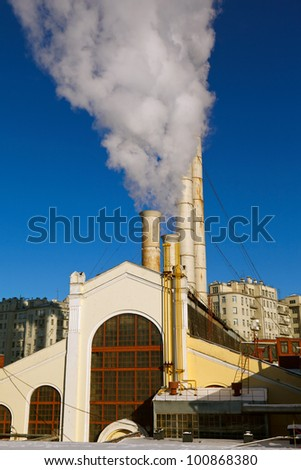 the smoke of the old power plant in the winter against the blue sky - stock photo