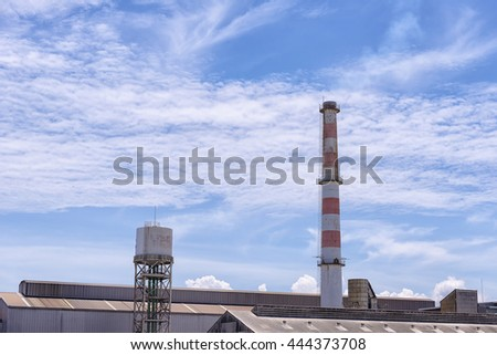The smokestack of the factory with the blue sky day. - stock photo