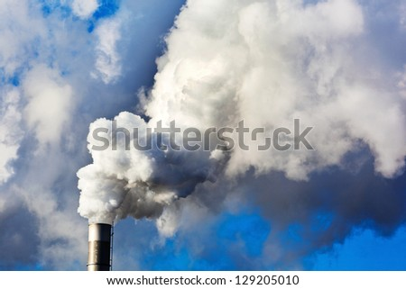 the smoking chimneys of a factory against a blue sky. smoke rises from chimneys white - stock photo