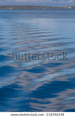 The smooth blue wake waves from behind a ship - stock photo