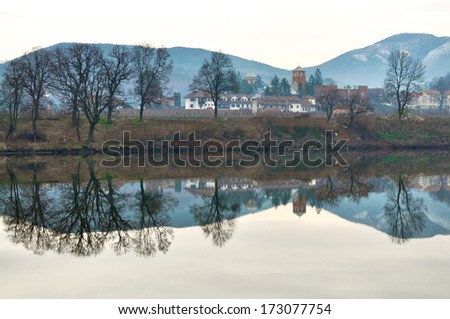The smooth surface of the lake with a reflection of the monastery - stock photo