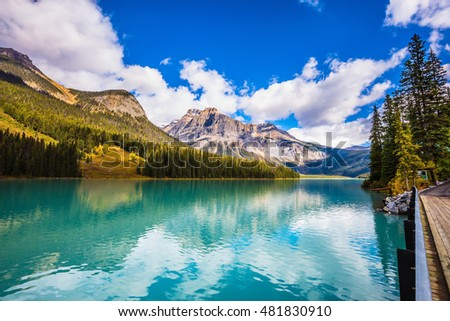 The smooth turquoise water in the wooded mountains. Sunny day in autumn. The concept of eco-tourism and active recreation. Charming mountain Emerald lake. Yoho National Park, Canada