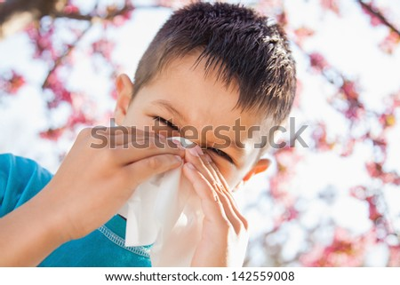 The sneezing little boy with having spring allergy - stock photo