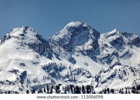 The snow capped peaks of Twin Peaks of the Wasatch mountains in Utah under clear blue sky's/ Snow Capped Wasatch Mountains - stock photo