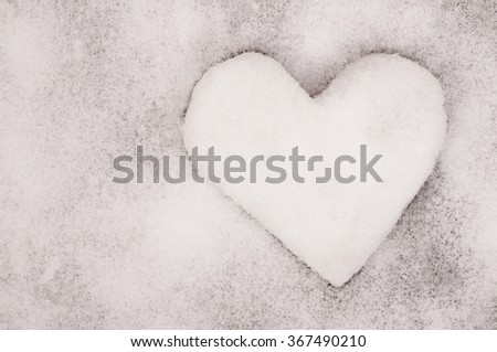 The snow heart on snow background.