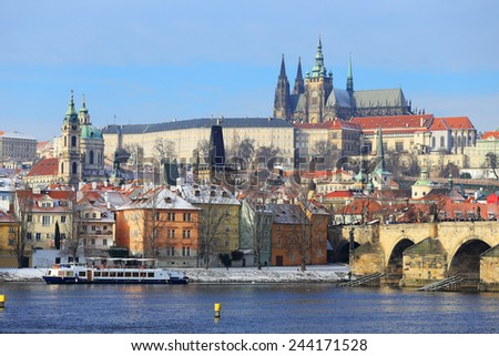 The snowy Prague gothic Castle with the Charles Bridge, Czech Republic - stock photo