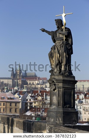 The snowy Prague gothic Castle with the Statue from the Charles Bridge, Czech Republic