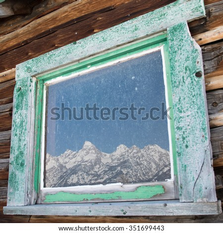 the snowy teton mountain range reflected in the window frame of a log cabin