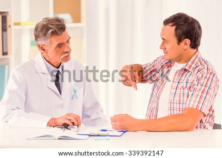 The social problem of male diseases. Portrait of doctor and patient man with a blue ribbon sitting in the office