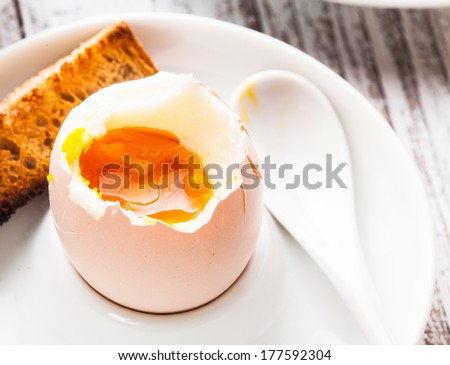 The soft-boiled egg in an eggcup with toasted bread - stock photo