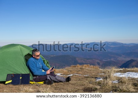 The solar panel attached to the tent. The man sitting next to mobile phone charges from the sun. - stock photo
